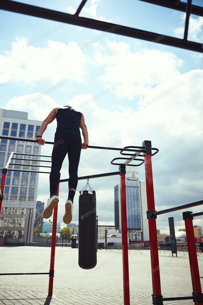 Silhouette of sportsman keeping balance on bar