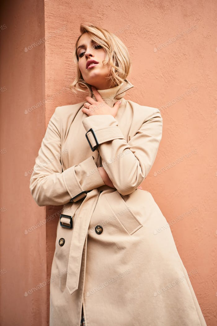 Beautiful stylish blond girl in beige trench coat sensually posing outdoor