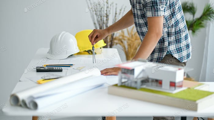 Draftsman is designing house plan, model houses and house plans with a safety helmet on the desk.