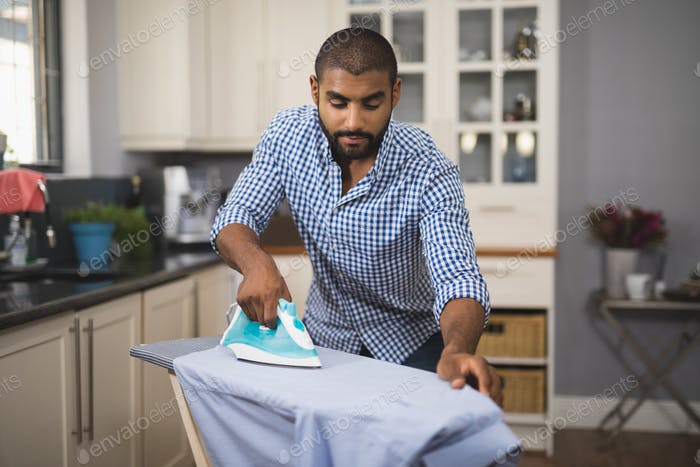 Young man ironing cloth in domestic kitchen