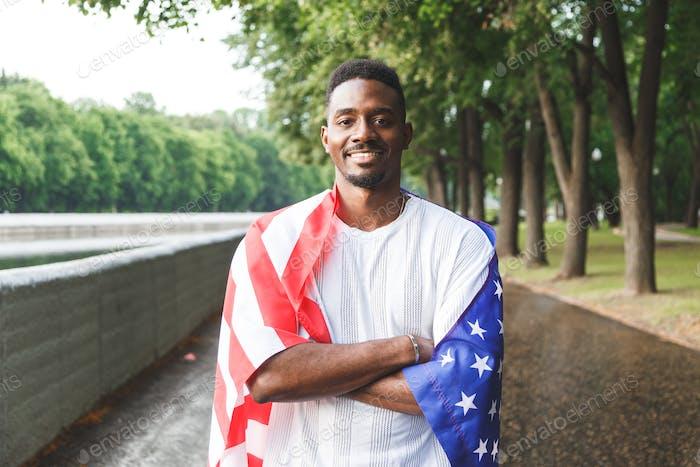 Afro amerikanischer Mann mit USA-Flagge auf seinen Schultern, Blick auf die Kamera, steht im Freien. Tag Sommer