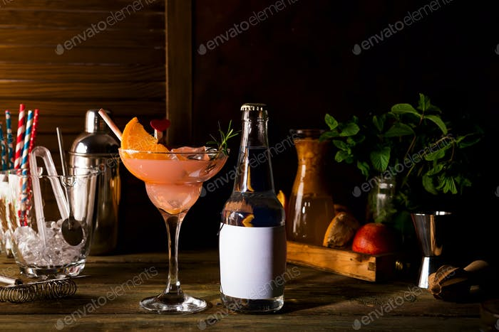 French daiquiri, alcohol cocktail with fresh orange and grapefruit juice with a bottle of tonic