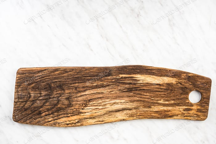 Empty wooden serving boad on marble table