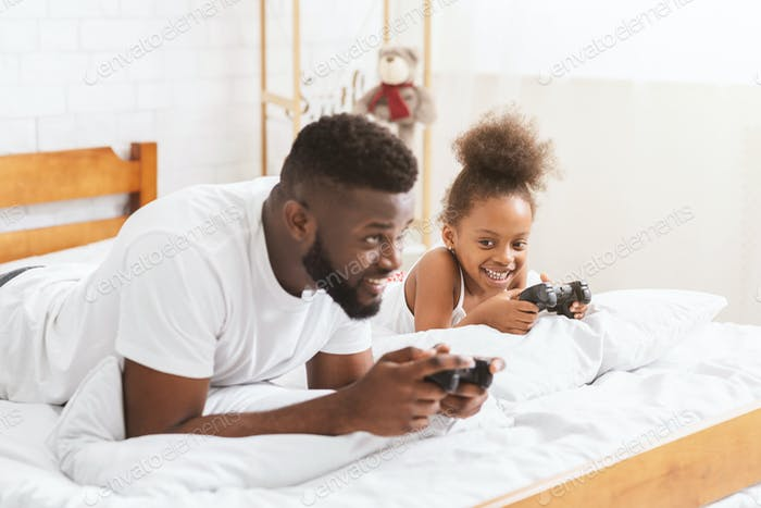 African man and his little girl playing on console with joysticks