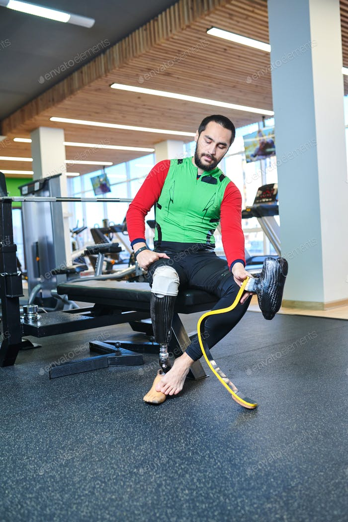 Man with amputated leg changing prosthesis