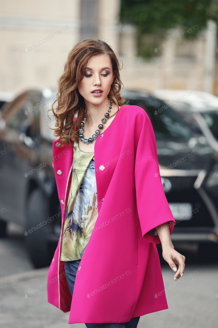 Slim beautiful girl dressed in a stylish summer fuchsia corol coat walks on a city street