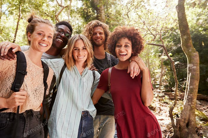 Five young adult friends hiking in a forest smiling to camera, three quarter length, close up
