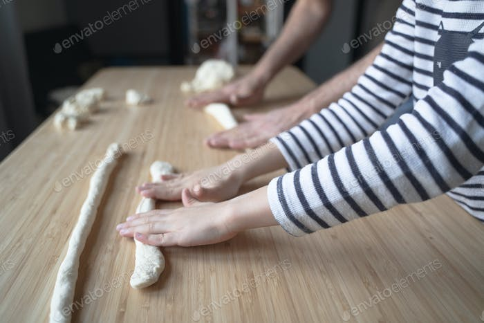 little Caucasian child working the dough with his father on a wood cutting board