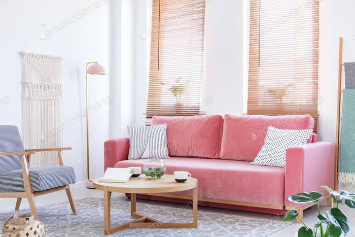 Patterned armchair next to pink sofa in bright flat interior wit