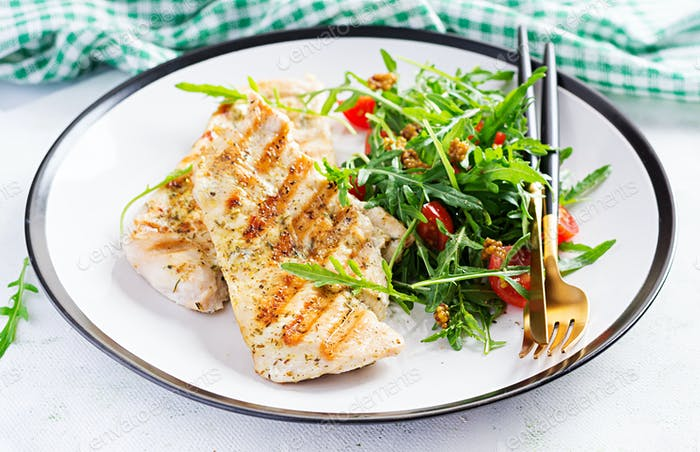 Grilled chicken fillet with fresh salad - arugula and tomato. Ketogenic food. Healthy lunch.