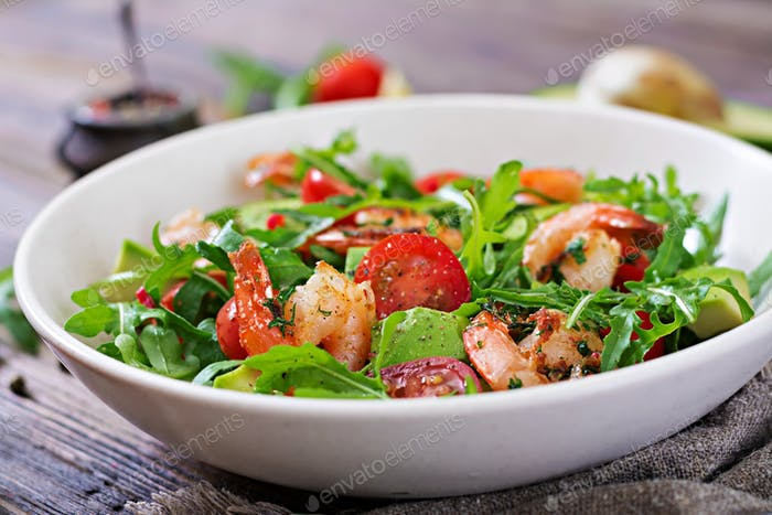 Fresh salad bowl with shrimp, tomato, avocado and arugula on wooden background close up