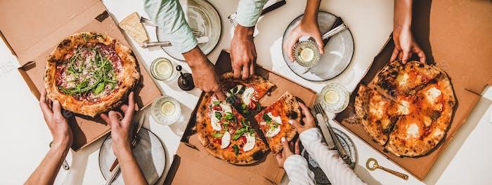 Pizzen in Kisten, Zitronengetränke und Völker Hände schneiden Pizzen