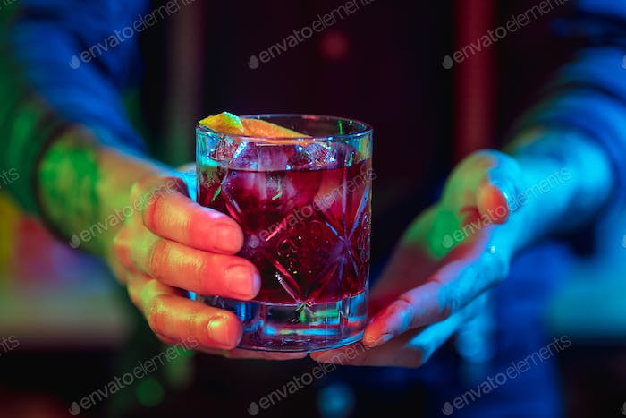 Close up of barman finishes preparation of alcoholic cocktail in multicolored neon light