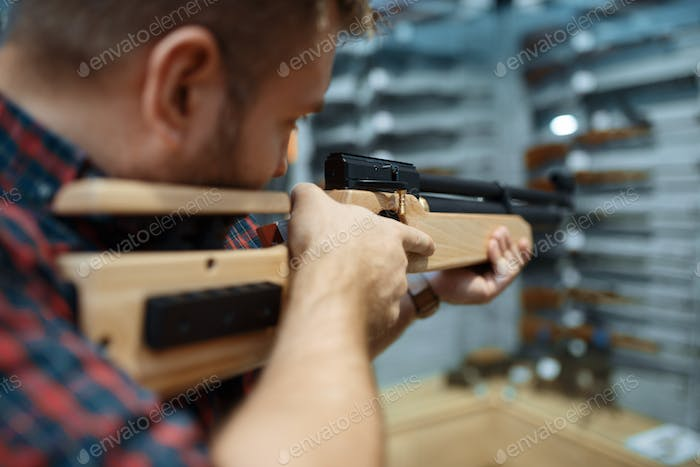 Male person with pneumatic rifle in gun shop