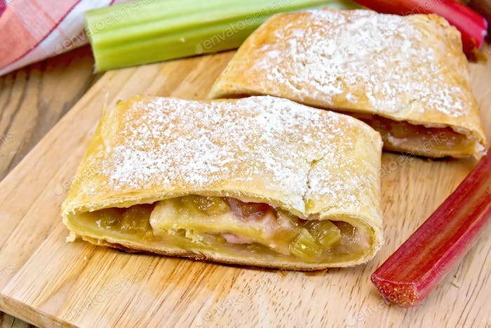 Strudel with rhubarb and napkin on wooden board