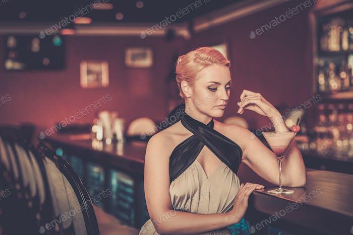 Schöne blonde Frau im Abendkleid sitzen in der Nähe Bartheke