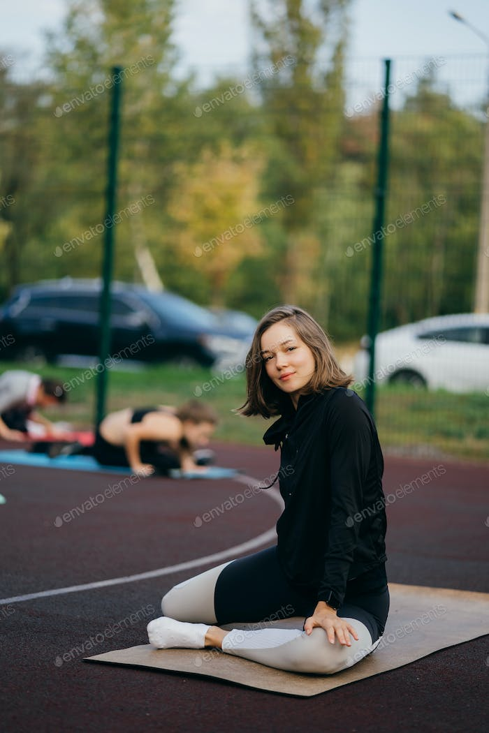 Young fit woman in sportswear trains outdoors on the playground