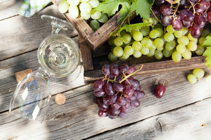White wine and grape on wooden table