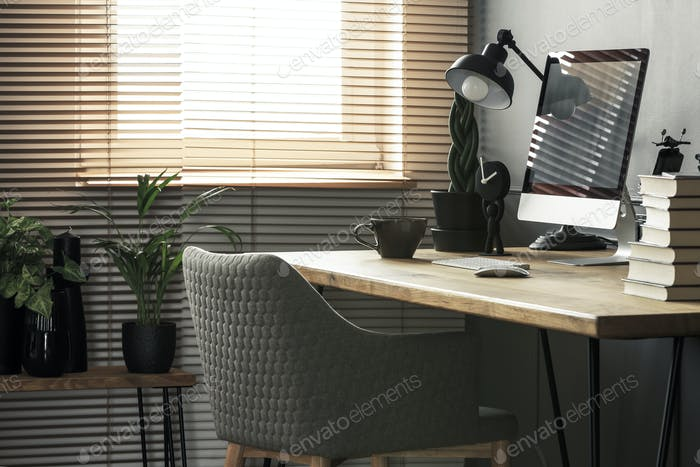 Grey chair at wooden desk with books and desktop computer in bri