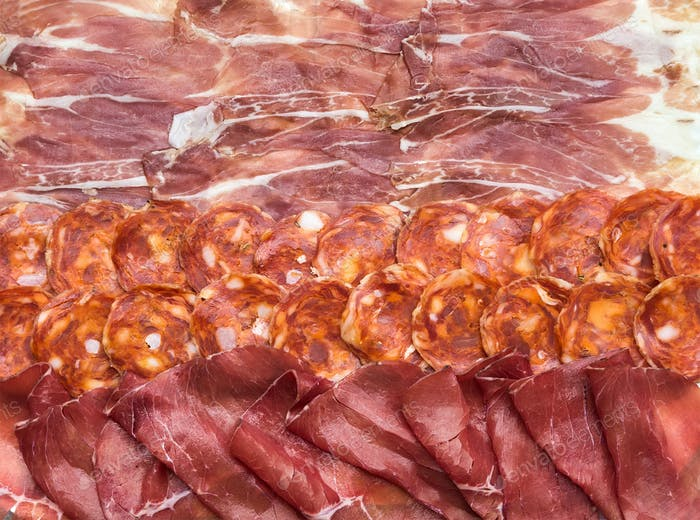 Composition of italian cured meat types. Salami, bresaola and Prosciutto di Parma slices, top view