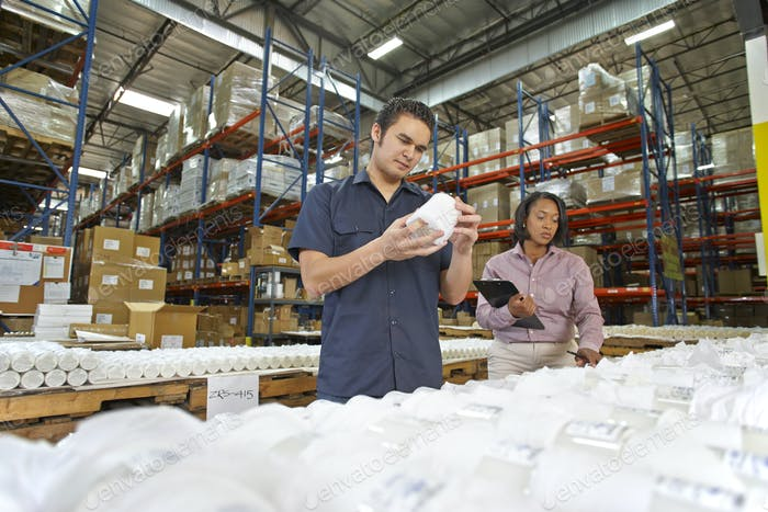 Factory Worker And Manager Checking Goods On Production Line