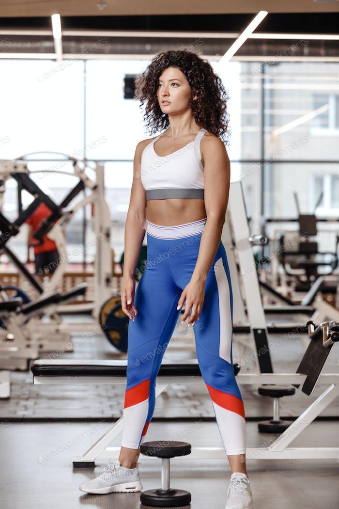 Schlankes Mädchen mit dunklen lockigen Haaren in einer Sportbekleidung gekleidet steht neben t der schweren Hantel in