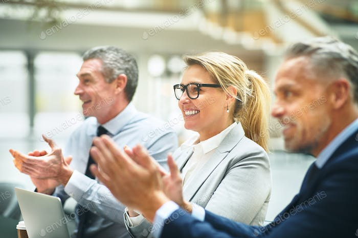 Mature businesspeople smiling and clapping after an office presentation
