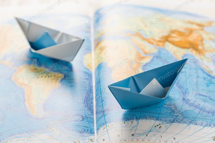 Paper boats on world map. Concept of traveling or military exercise.