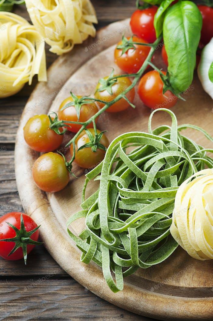Rohe Nudeln, Tomaten und Basilikum auf dem Holztisch