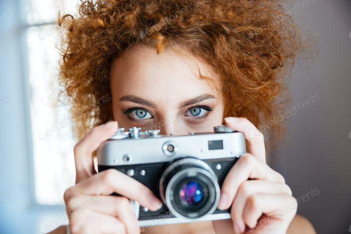Attractive redhead woman photographer using old camera
