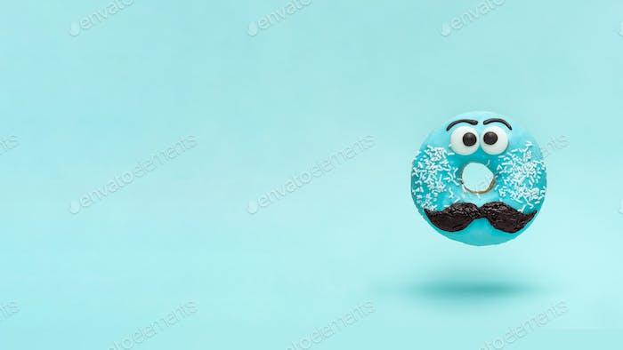 Blau glasierter Donut mit Schnurrbart fliegen