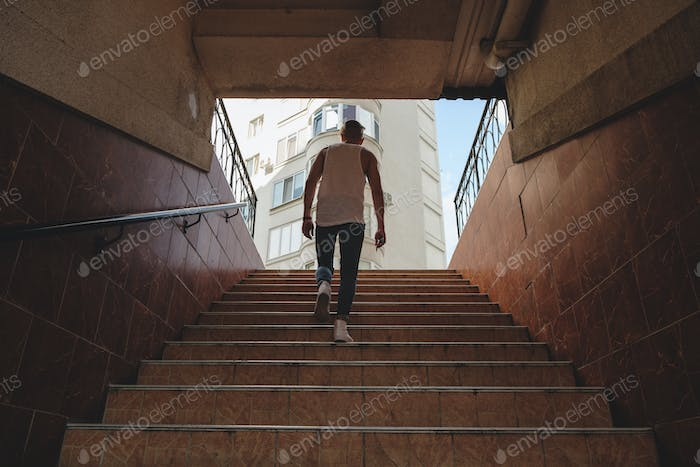 Young man climbing stairs in pedestrian subway