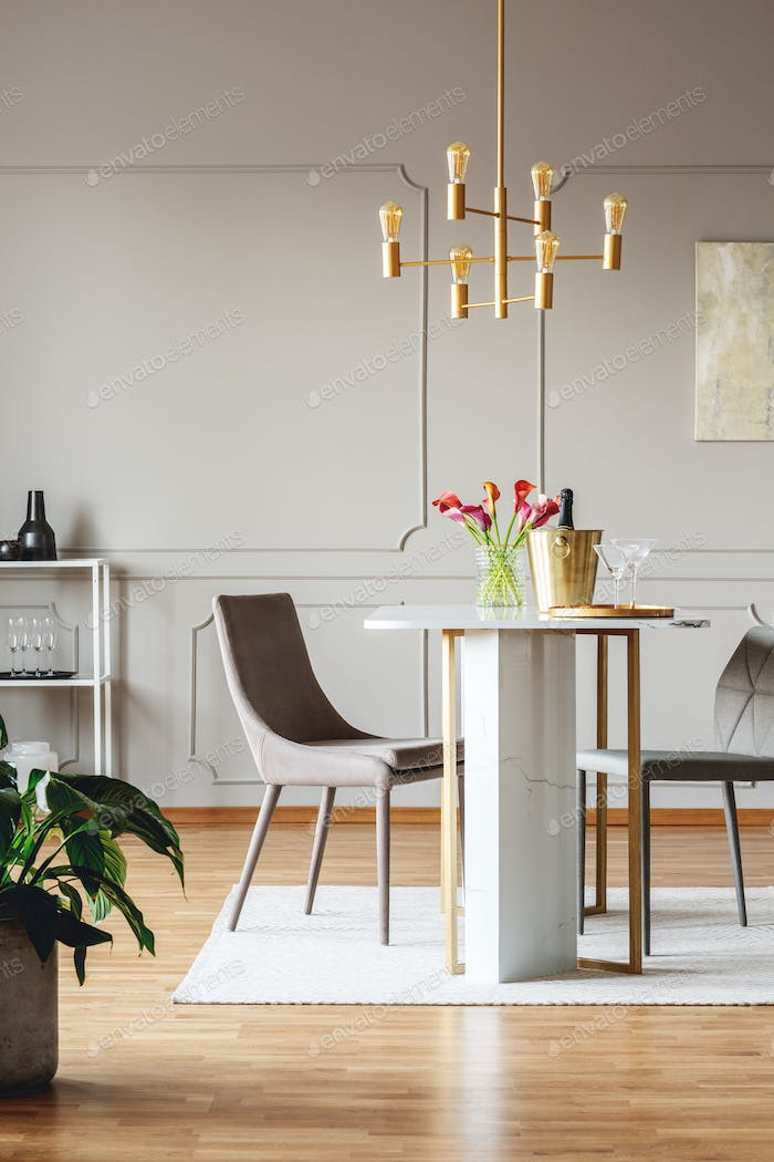 Chairs at dining table with flowers in bright apartment interior