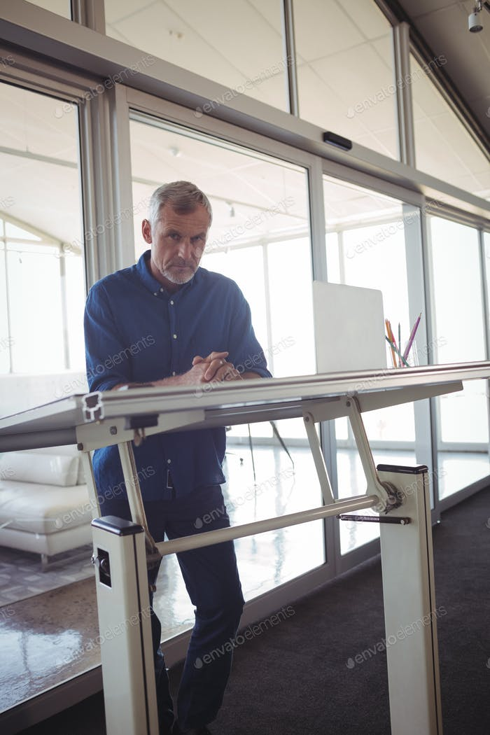 Mature businessman standing by workbench in office