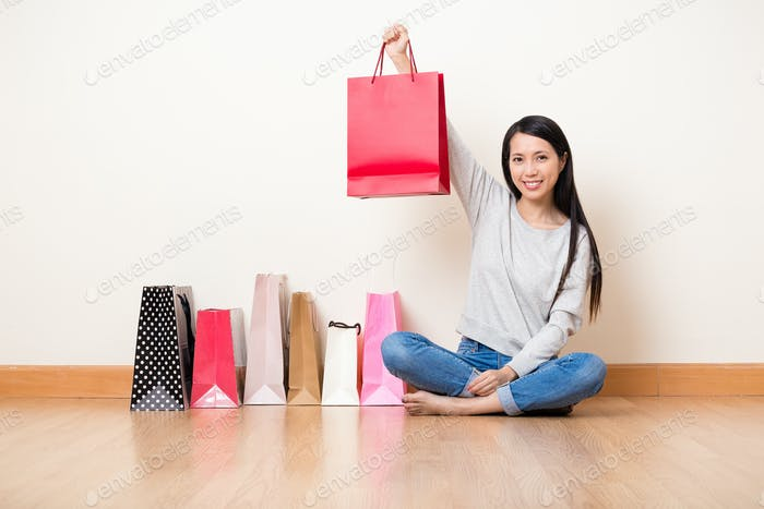 Woman showing the shopping bag after crazy shopping