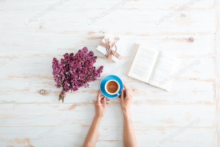 Hands of woman drinking coffee and reading book on table