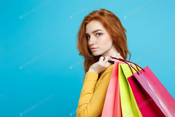 Shopping Concept - Close up Portrait young beautiful attractive redhair girl looking at camera. Blue