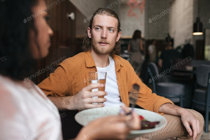 Man with blond hair and beard dreamily looking at girl in restaurant