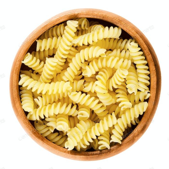 Girandole torsades pasta in wooden bowl over white