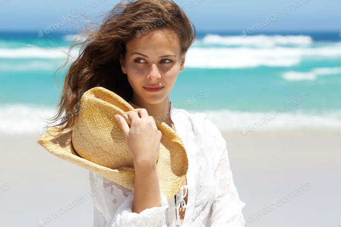 Sensual young woman with hat at the beach