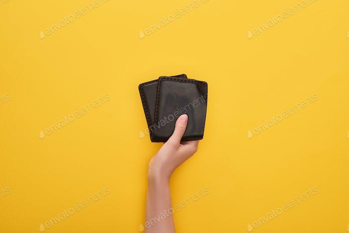 Vista recortada de la mujer sosteniendo cartera sobre fondo amarillo