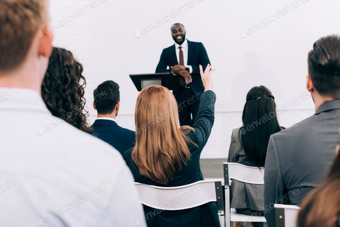 african american lecturer talking to audience during seminar in conference hall, participant raising