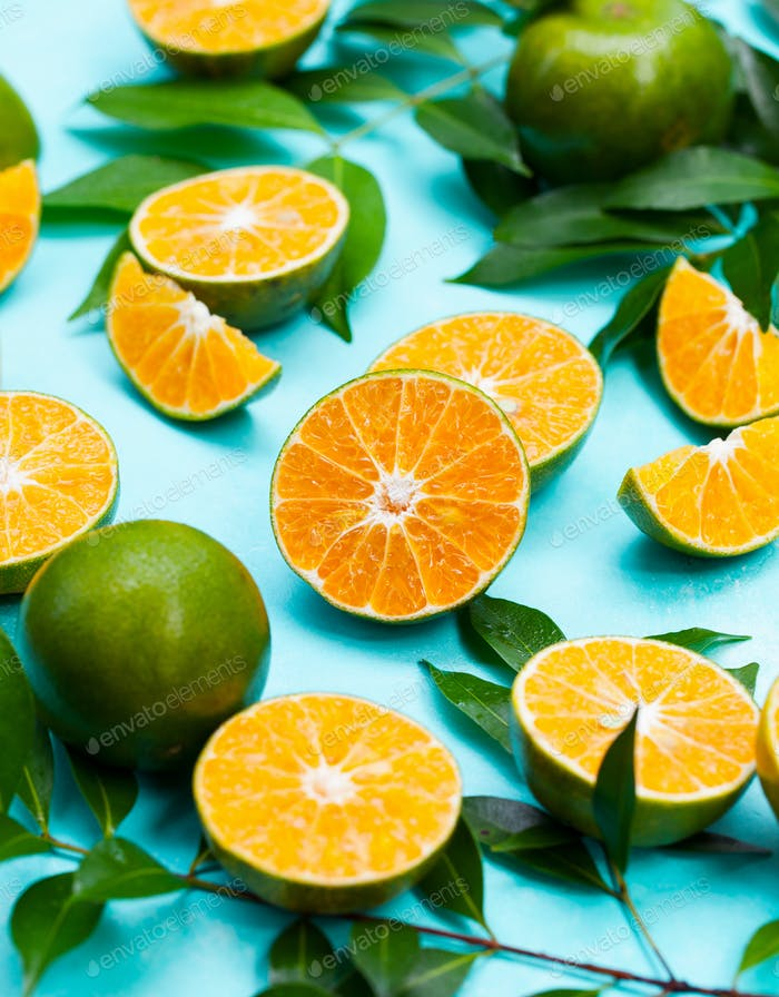 Oranges with Green Leaves on Blue Background. Close up.