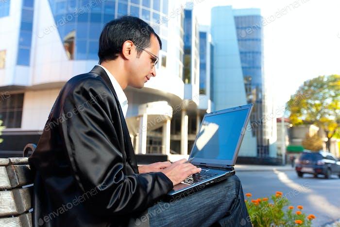 Man tippt auf Laptop auf der Straße