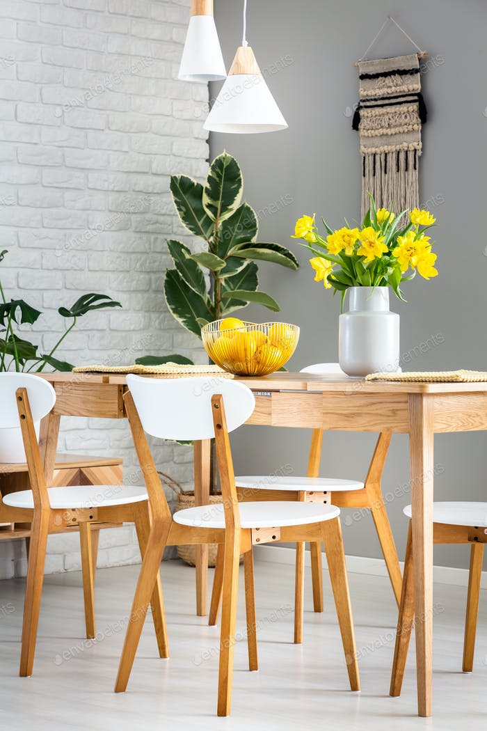 White chairs and lamps in dining room interior with daffodils an