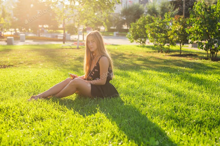 beautiful young woman listening music in the park