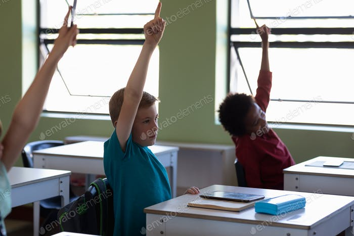 Group of school children sitting at desks and raising their hands to answer