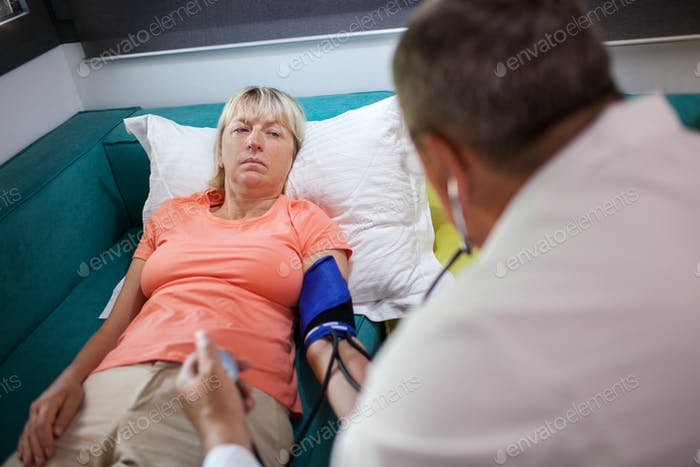 Doctor checking womans blood pressure