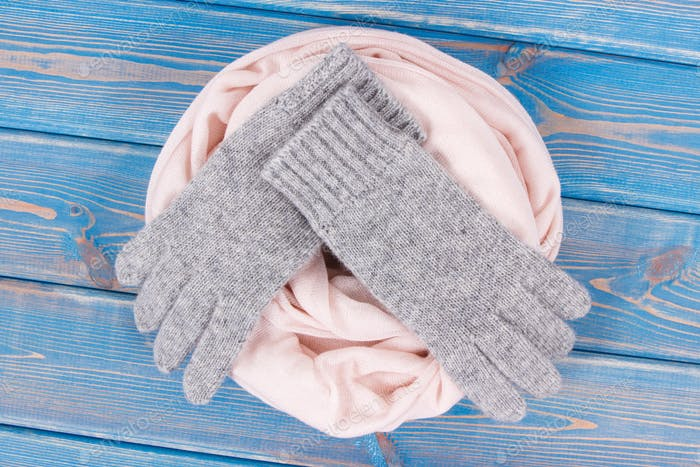 Woolen womanly gloves and shawl for autumn or winter on old boards