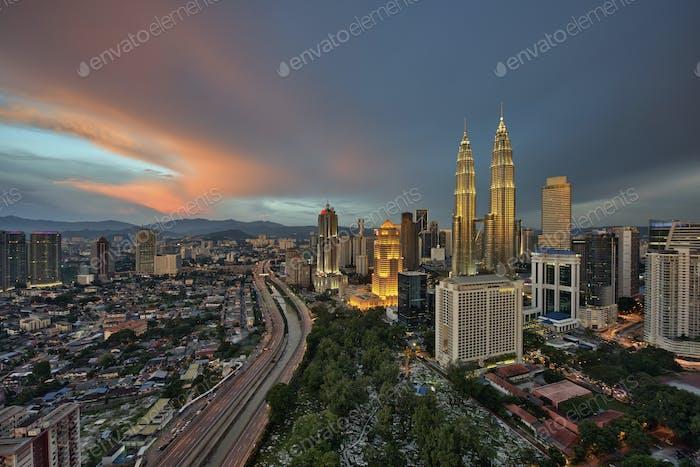 Stadtbild von Kuala Lumpur, Malaysia in der Dämmerung, mit beleuchteten Petronas Türmen in der Ferne.